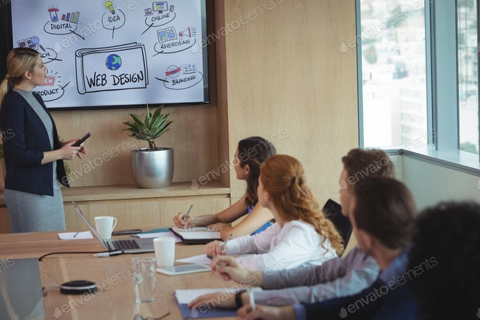 Businesswoman explaining plant to team during meeting