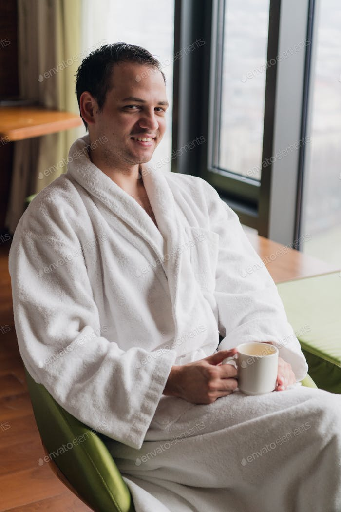 Morning portrait of handsome young man with cup of coffee
