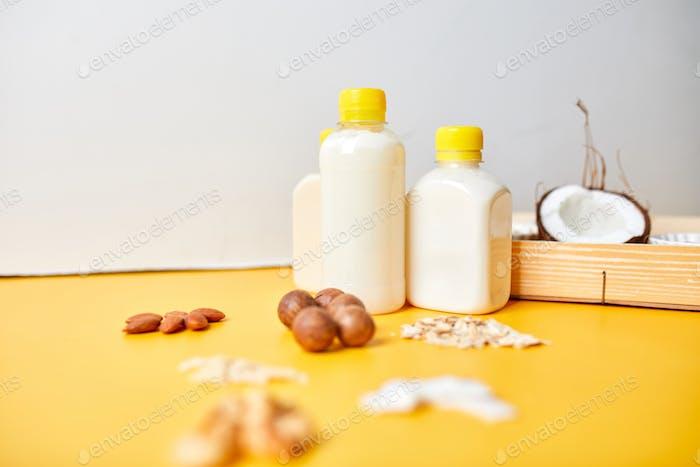 Alternative Arten von veganen Milch in Flaschen auf gelbem Hintergrund