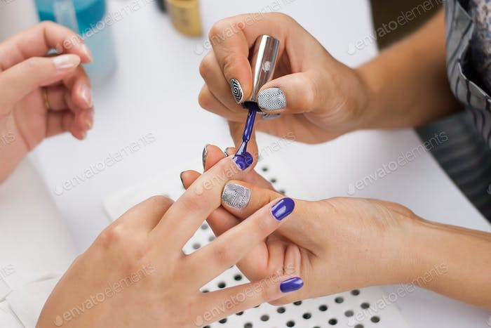 Close Up shot of a woman in a nail salon receiving a manicure by a beautician, nail polish