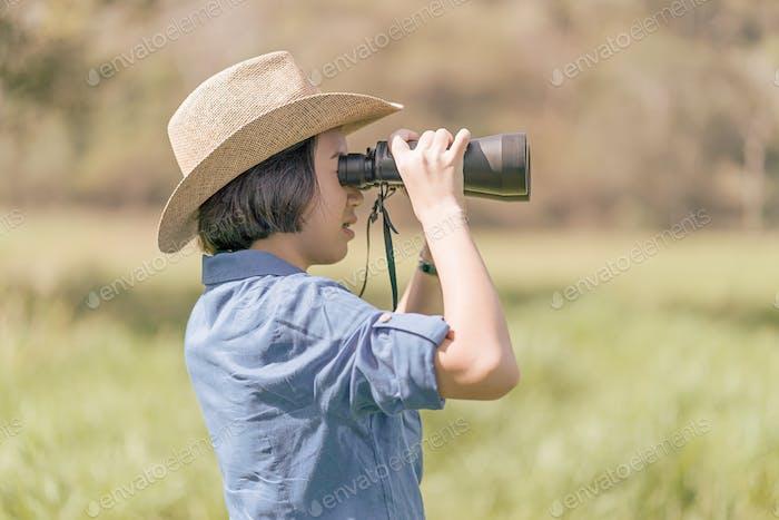 Woman wear hat and hold binocular in grass field-6