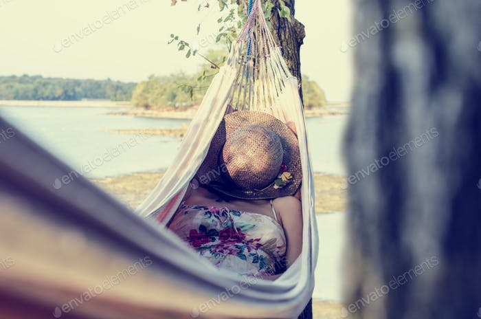 Woman relaxing in a hammock, next to a lake
