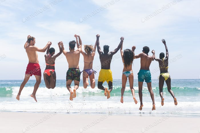 Rear view of diverse group friends enjoying and jumping in water at beach on a sunny day
