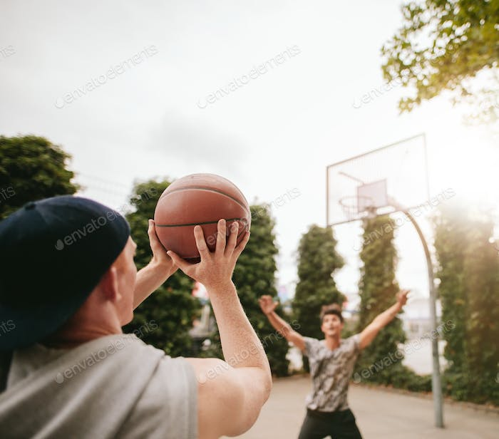 Friends playing basketball against each other