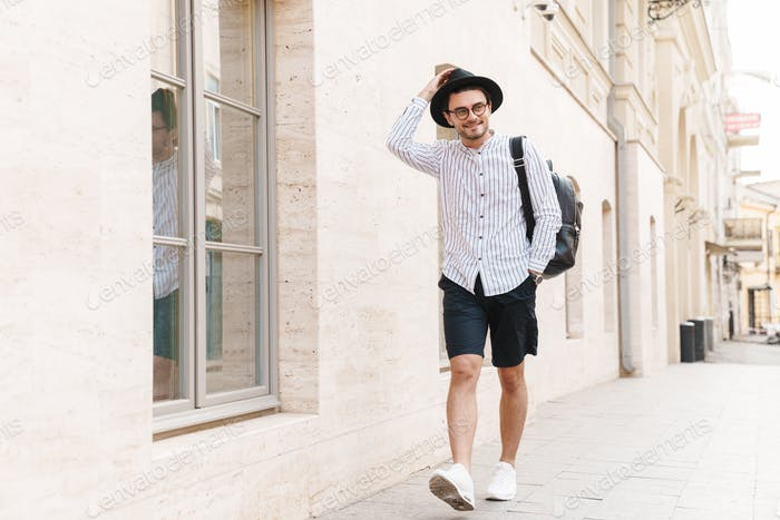 Photo of happy unshaven man wearing eyeglasses and black hat looking aside and smiling
