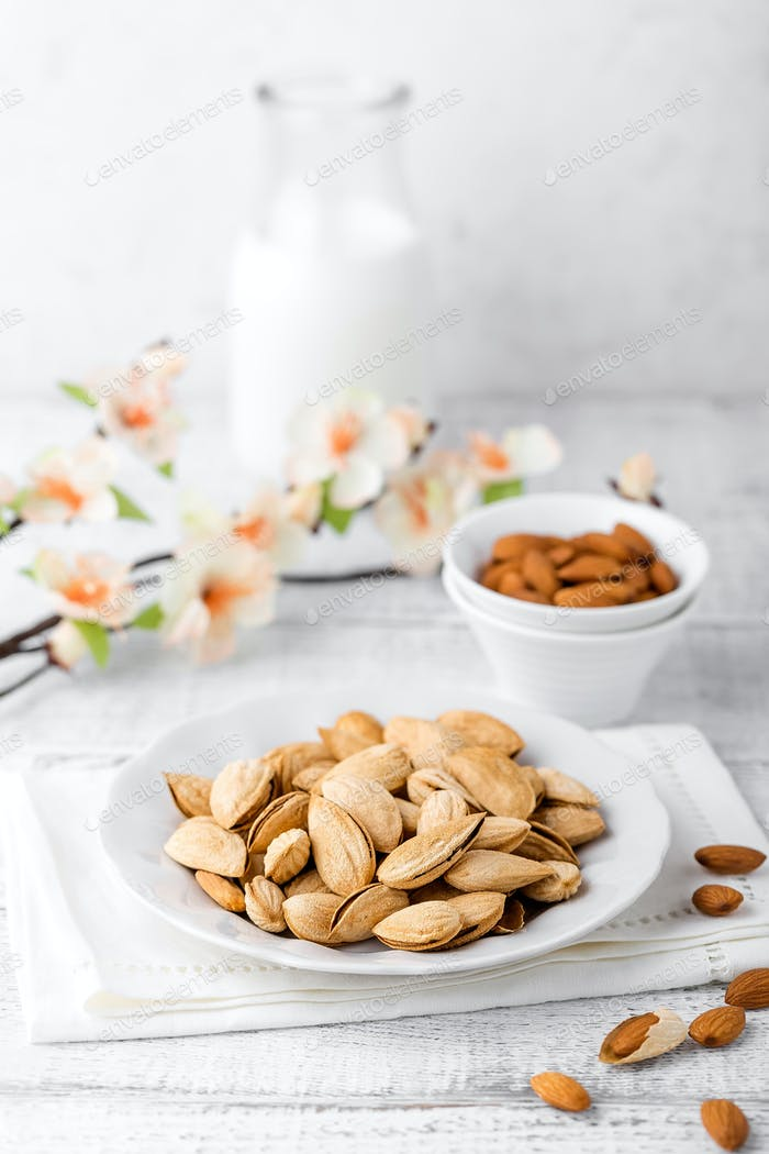 Almond nuts and milk on white background