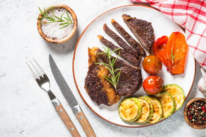 Grilled beef steak with vegetables top view