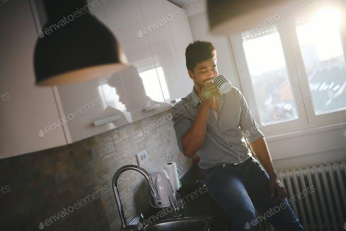 Handsome african american man drinking coffee in kitchen