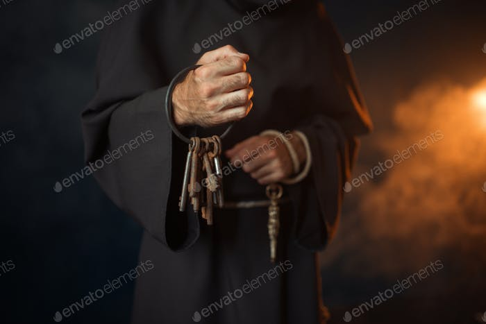Medieval monk holds a bunch of keys in hands