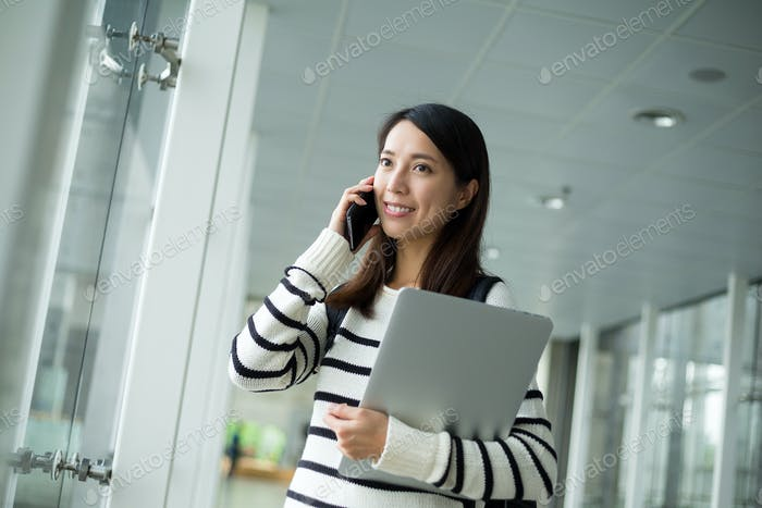 University student hold with laptop computer and talk to mobile phone