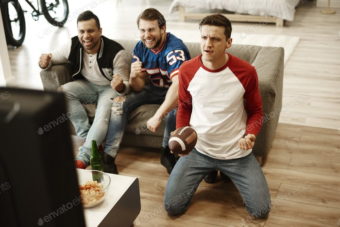 Male friends watching American football