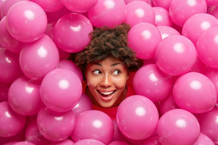 Beautiful happy curly dark skinned woman sticks head through heap of pink inflated balloons smiles j