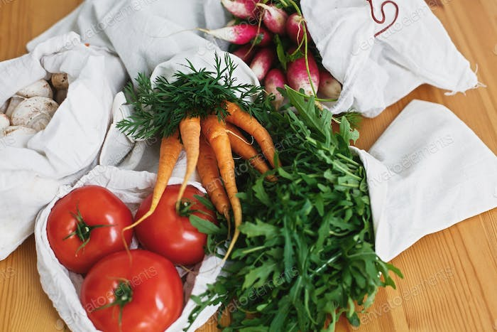 Zero waste grocery shopping concept. Reusable eco friendly bags with fresh vegetables carrots