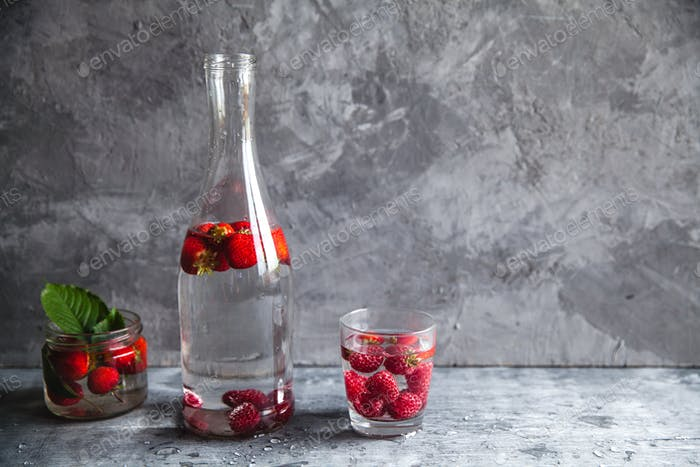 Strawberries in water on a dark gray background. Healthy food, fruit. A bouquet of flowers