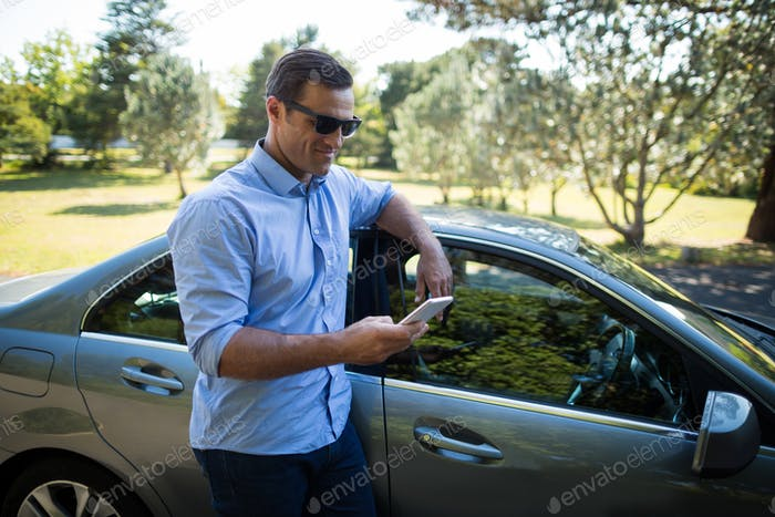 Young man holding mobile phone by car