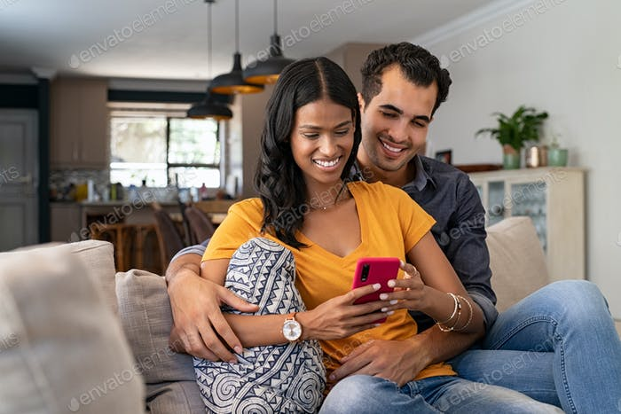 Loving indian couple using smartphone togetrher