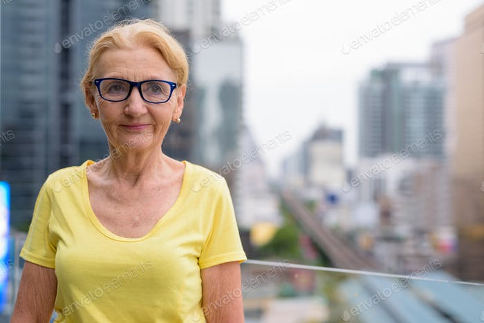Beautiful senior woman with blond hair against view of the city