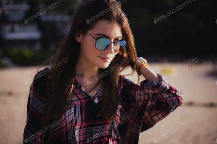 Cerca de la Playa Vertical de Alegre hipster rubia. Chica salvaje en Playa de verano con gafas de sol
