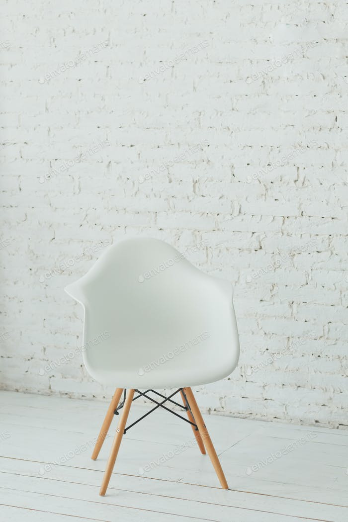 Interior with white modern chair and a white brick wall