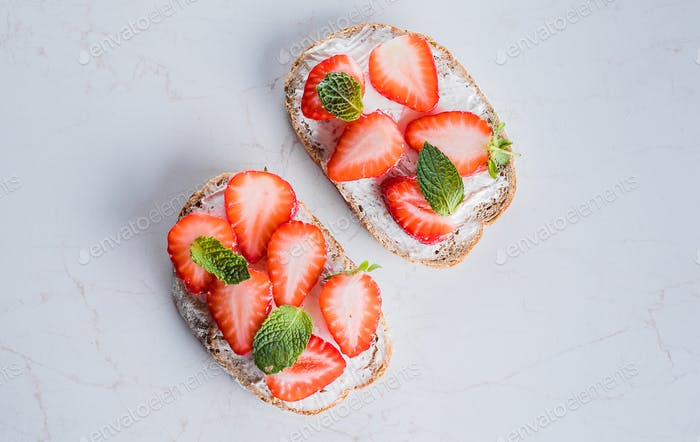 Two toasts or bruschetta with strawberry and mint on cream-cheese on wooden table background