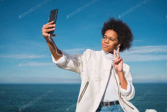 Young woman taking selfies with phone.