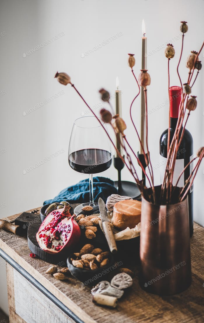 Red wine, appetizers, candles and flowers over wooden kitchen counter
