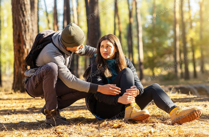 Young guy rubbing his girlfriend injured leg, hiking together