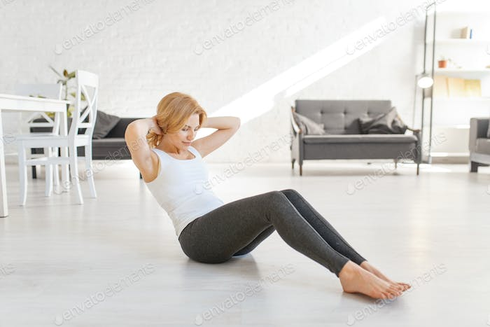 Yuong woman doing morning exercise in living room