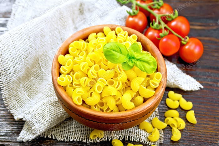 Elbow macaroni in bowl with tomatoes on dark board