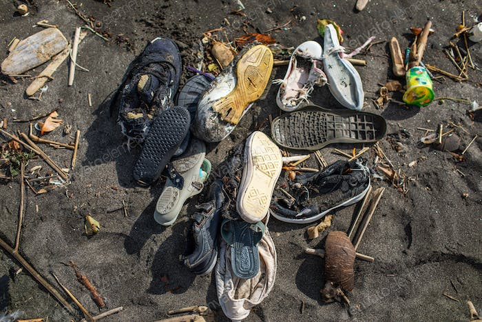 Environmental pollution. Heap of used rubber shoes on the beach in Bali, Indonesia.
