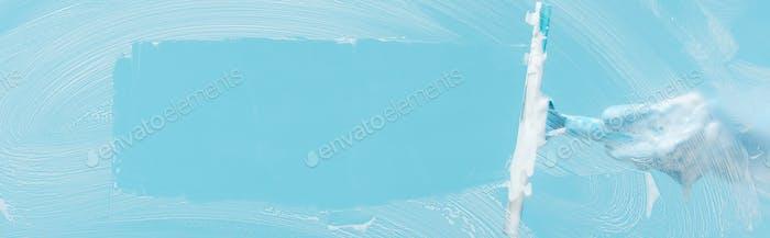 Panoramaaufnahme einer Frau im Gummihandschuh, der Glas mit Rakel auf blauem Hintergrund reinigt