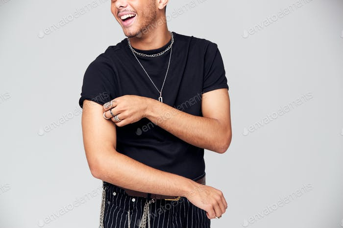 Studio Portrait Of Young Man With Skin Pigmentation Disorder Rolling Up Sleeves Of T Shirt