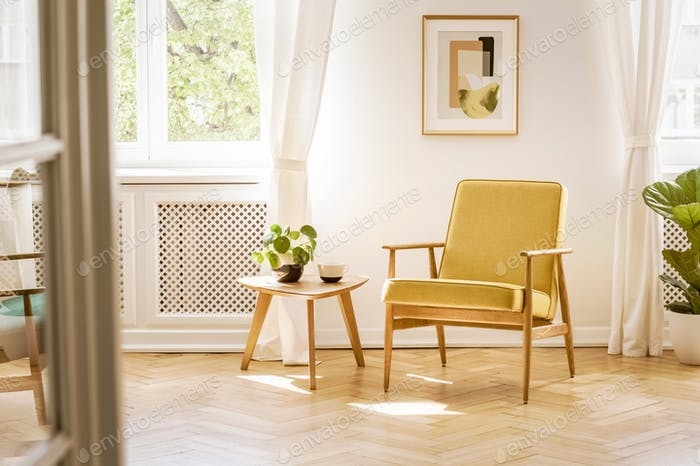 A retro, yellow armchair and a wooden table in a beautiful, sunn
