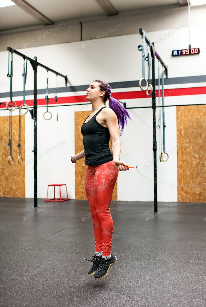 Fit woman athlete exercising with a skipping rope