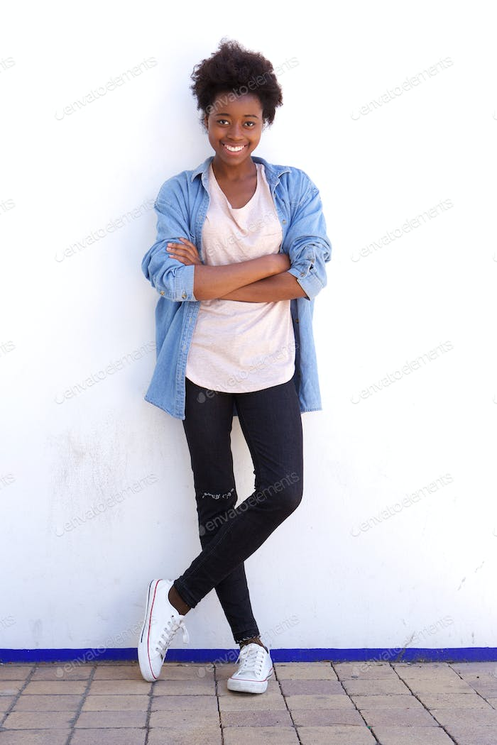 Full length smiling young women with arms crossed standing against white wall