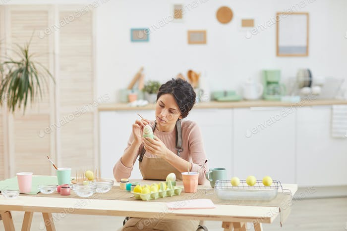 Young Woman Painting Easter Eggs in Kitchen