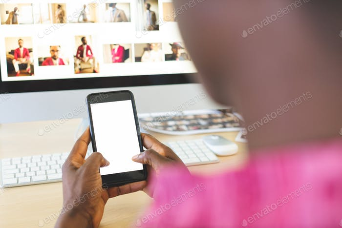 Rear view of young African-American businessman using mobile phone at desk in office