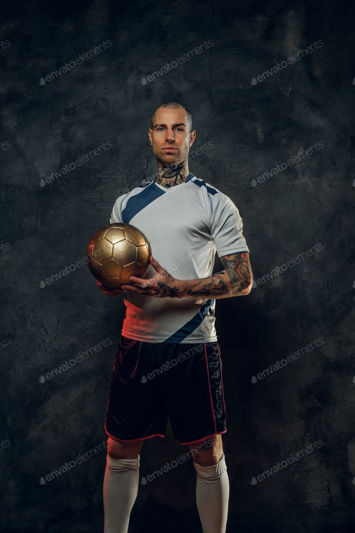 Bold and handsome soccer player holding a golden soccer ball