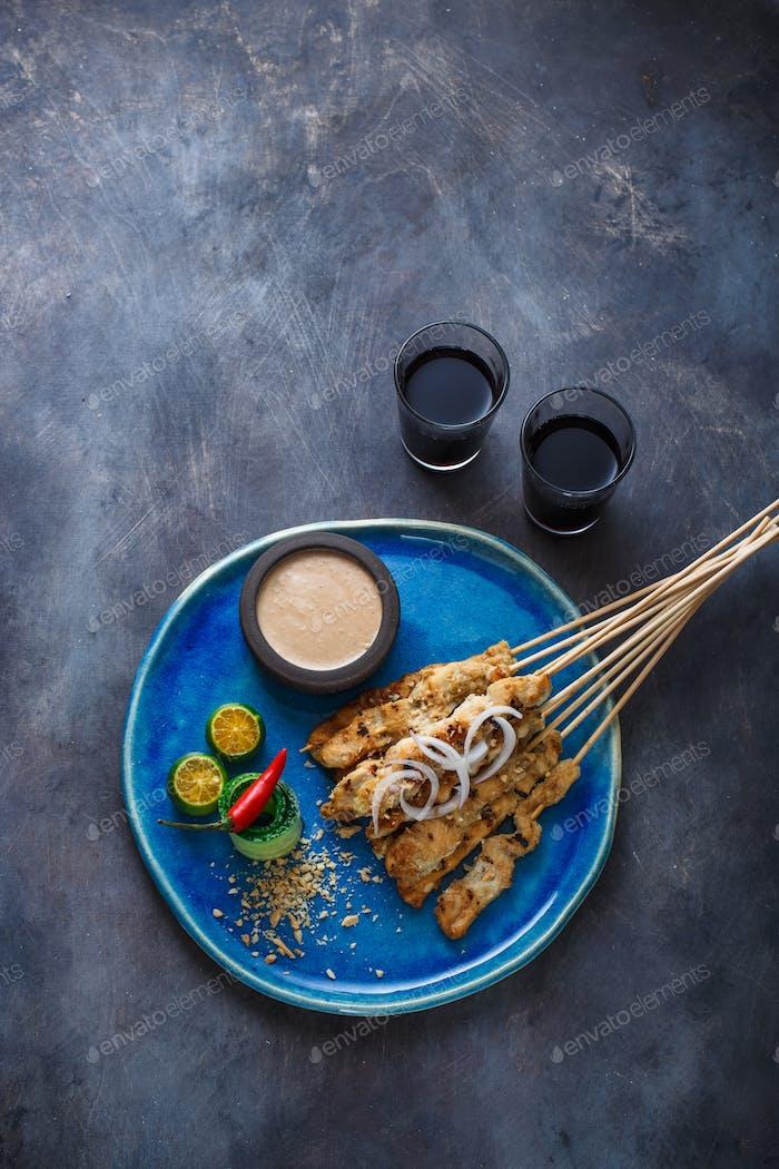 Indonesische Hähnchenspieße mit Erdnuss-Sauce und Salat, Draufsicht, Copyspace