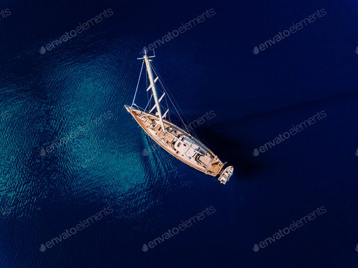 Aerial view to Yacht in deep blue sea.