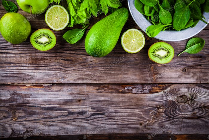 green vegetables: kiwi, spinach, avocado, lime, celery on a rustic wooden background