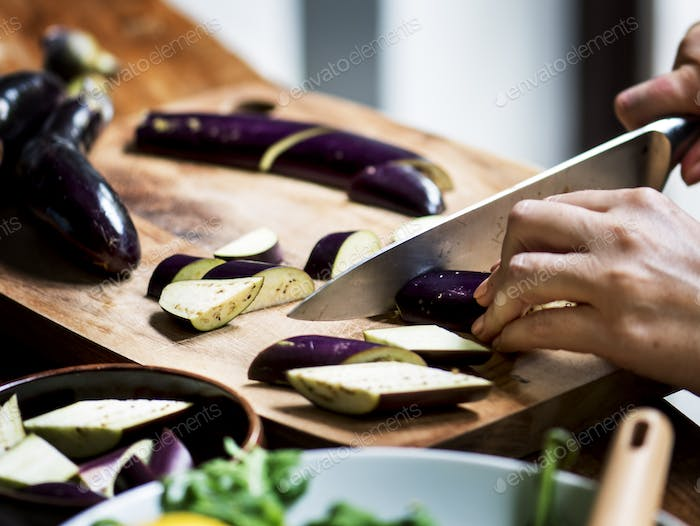 Closeup of hand with knife cutting eggplant