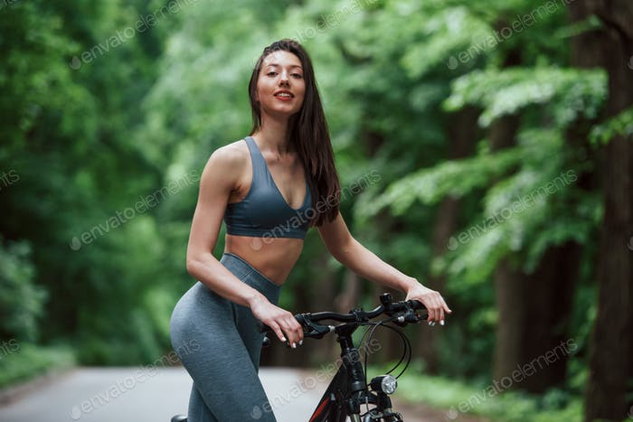 Positive emotions. Female cyclist standing with bike on asphalt road in the forest at daytime