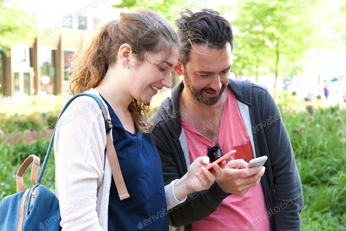 Cheerful couple standing outside in urban park with mobile phones