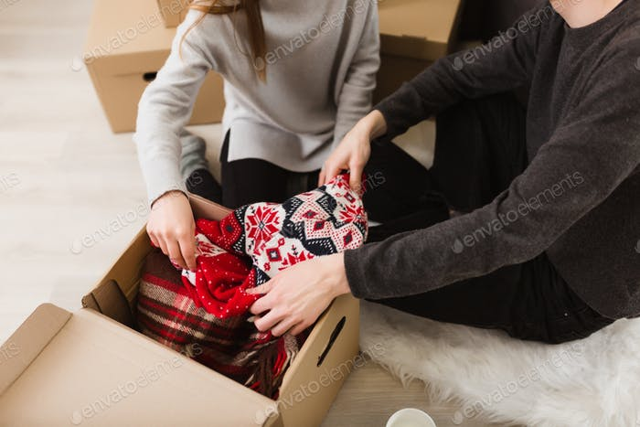 Close up photo of man and woman hands opening gift box with new sweater together isolated