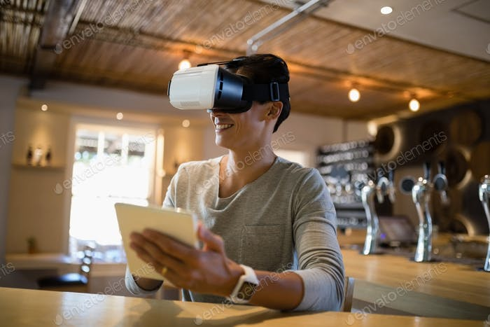 Man using virtual reality headset and digital tablet in restaurant