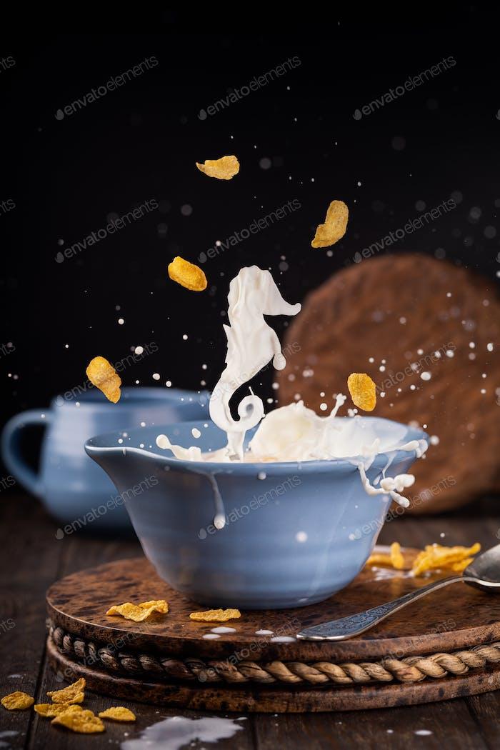 Blue bowl of corn flakes with milk splash