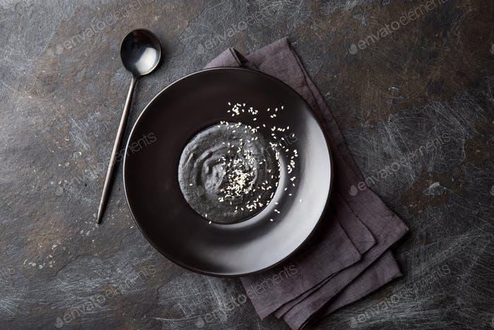 Chinese tradition food. Black sesame sweet soup in black plate.