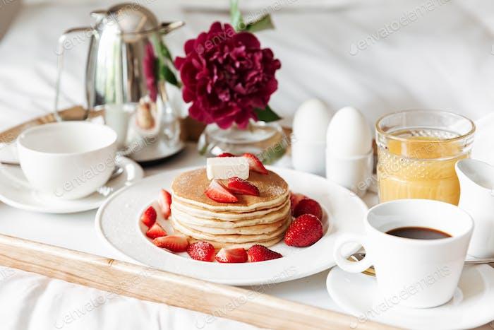 Desayuno en la cama con ropa blanca. Panqueques, huevos duros, café
