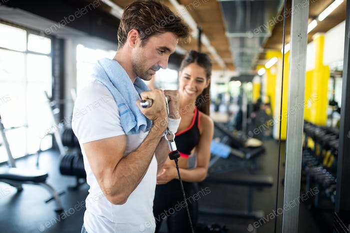 Sporty man doing weight exercises with assistance of her personal trainer